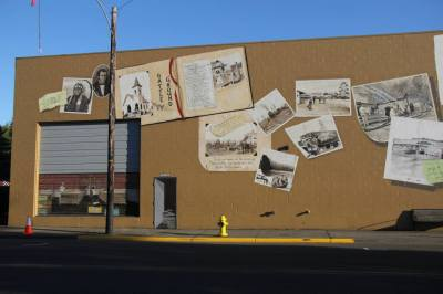 """The first phase consisted of the roll-up door, the scrapbook and the loose scrapbook page and the two pictures connected to it, as well as the man doors at both ends of the building.  This shows just the one to the right of the roll-up door.  I """"opened"""" them to reveal what would have been there at one point in the history of the building."""