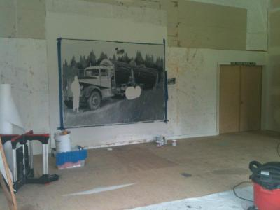 """Here you can see the roll of pellon to the far left and the logging truck picture under construction.  In order to save time and keep the proportions correct, I used my trusty, retro, overhead projector to transfer the image.  Tracing the image with chalk allowed me to """"edit"""" any lines I needed, especially if the projector warped things too much.  Then I'd use the enlarged  copy of the picture in hand as my reference to paint from."""